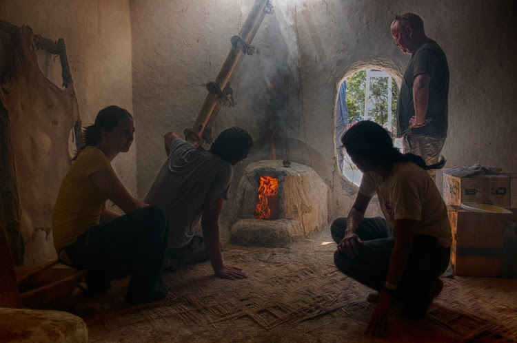 Image of researchers testing the effects of smoke from a burning oven fire in a replica house at Çatalhöyük.